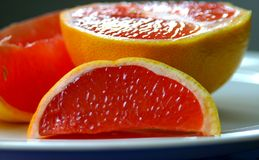 Pink Grapefruit slices on plate Stock Photos