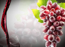 Pink grapes and pouring wine on the grey background Stock Photography