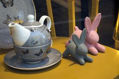 Pink and gray plastic rabbits and a kettle with a cup in the shop window. Poznan, Poland, April 30, 2018: Pink and gray plastic rabbits and a kettle with a cup royalty free stock images