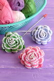 Pink, green and blue crochet flowers decorated with beads. Cotton yarn skeins in basket, hook and bright knitted roses Royalty Free Stock Image