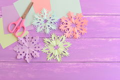 Pink, green, blue and purple paper snowflakes, colored paper sheets, scissors on wooden background with copy space for text Royalty Free Stock Photography
