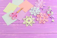 Pink, green, blue and purple paper snowflakes. Paper snowflake set, colored paper sheets and scraps, scissors on wooden background Royalty Free Stock Photo
