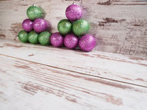 Pink and green christmas balls in a stack over wooden background Stock Images