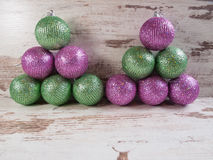 Pink and green christmas balls in a stack over wooden background Royalty Free Stock Images