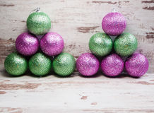 Pink and green christmas balls in a stack over wooden background Royalty Free Stock Photo