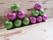 Pink and green christmas balls in a stack over wooden background Royalty Free Stock Image