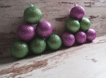 Pink and green christmas balls in a stack over wooden background Royalty Free Stock Photos