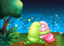 A pink and a green couple monsters hugging each other at the pat Royalty Free Stock Photos