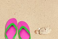 Pink and green flip flops on the beach Royalty Free Stock Images