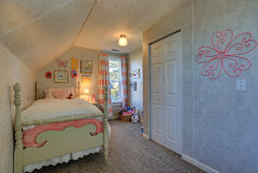 Pink and green girl`s attic bedroom with sloped ceiling. Over poster bed and small window dressed in pink stripe curtains. Northwest, USA Stock Photography