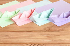 Pink, green, lilac, blue paper origami ships toys on wooden table with empty space for text. Colored paper sheets Stock Image