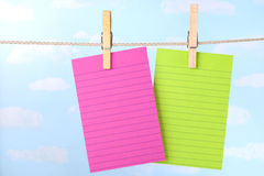 Pink and green notes on clothesline Stock Photography