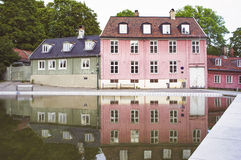 Pink and green old houses reflected in a pond. Stock Photos