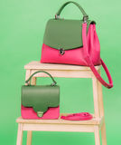 Pink and green one styled woman`s handbags standing on a chair Royalty Free Stock Image