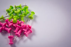 Pink and green push pins on white background stock images