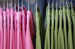 Pink and green shirts. On a clothes-hanger stock image