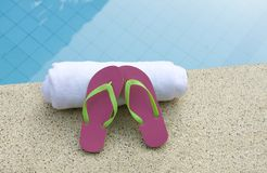 Pink and green shoes white towel swimming pool Stock Photo