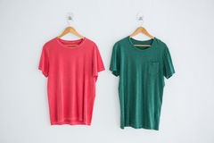 Pink and green t-shirts hanging on hanger Stock Image