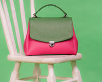 Pink and green woman`s handbag standing on a chair Stock Images
