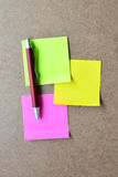 Pink, green, yellow note paper and red pen on wooden background. Royalty Free Stock Image