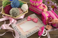 Pink greeting card with baby knitting things Royalty Free Stock Image