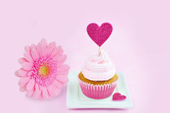 Pink greeting card with cupcake, red heart and pink gerbera. Royalty Free Stock Images
