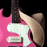 Pink Guitar with Girl's Western Hat Stock Photo