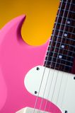 Pink Guitar Isolated On Gold. An electric pink guitar isolated against a gold or yellow background in the vertical format Royalty Free Stock Images