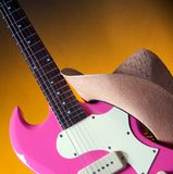 Pink Guitar and Western Hat. An electric pink guitar with a girl's or ladies western hat isolated against a gold or yellow background in the square format Royalty Free Stock Images