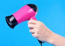 Pink hair dryer in the female hand Royalty Free Stock Photo