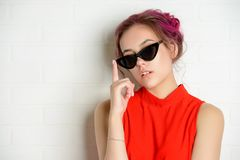 Pink haired girl. Pretty pink-haired girl in bright summer clothes and sunglasses posing on a light background. Fashion, beauty. Optics style. Youth style royalty free stock photography