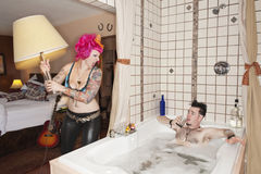 Pink haired woman throwing lamp on man in the bathtub
