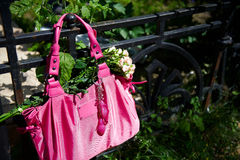 Pink handbag and a bouquet of roses Royalty Free Stock Photos