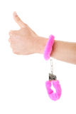 Pink handcuff. Young caucasian man hand with pink handcuff Royalty Free Stock Photo