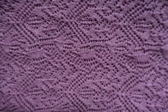 Pink handmade lacy knitting fabric. From above royalty free stock photo