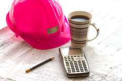 Pink Hardhat 2. A pink hardhat, calculator and pencil on calculation sheets and construction drawings, with a cup of black coffee Woman in the Engineering and stock photos