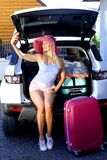 Pink hat blue baggage girl woman travel suitcase red color background shorts blonde summer trunk car smile road trip device phone stock photos