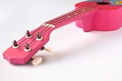 Pink Hawaiian ukulele. Closeupshot of a Pink Hawaiian ukulele on white background Royalty Free Stock Photography