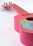 Pink Hawaiian ukulele. Closeupshot of a Pink Hawaiian ukulele on white background Stock Photo