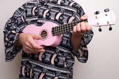Pink Hawaiian Ukulele Love Song. A Hawaiian shirt clad boy strums a pink ukulele as he sings a pretty love song stock image