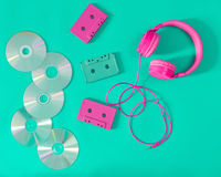 Pink headphones and audio cassettes with CDs. On a turquoise background Stock Images