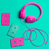 Pink headphones and audio cassettes with CDs. On a turquoise background Royalty Free Stock Images