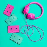 Pink headphones and audio cassettes with CDs. On a turquoise background Stock Image