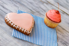 Pink heart biscuit and cupcake. Confectionery on checkered napkin. Tasty dessert for two. Let's celebrate together royalty free stock image
