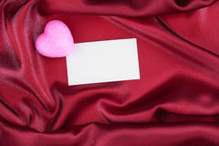 Pink heart and blank white post cards, empty postcard, lies on red silk. View from above Royalty Free Stock Images