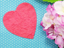 Pink heart on blue polka dot background and beautiful flower Royalty Free Stock Images