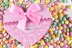 Pink heart box with bow above colorful round candies Stock Photos