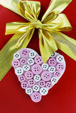 Pink heart from buttons on a red background with a bow (backgrou Royalty Free Stock Photo