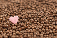 Pink heart on chocolate balls background, shallow depth of field. Stock Photos