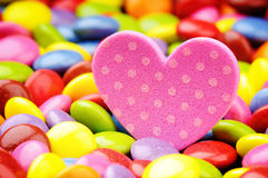 Pink heart and colorful smarties Royalty Free Stock Photography